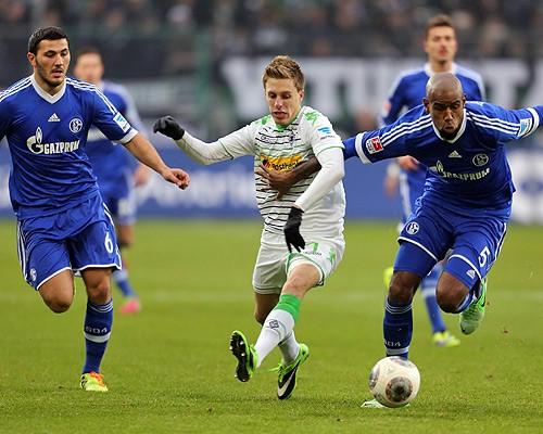 Sead Kolasinac (izq.) y Felipe Santana (der.), disputan un balón con Patrick Herrmann (cen.), cel Borussia Mönchengladbach. Foto: Getty Images.