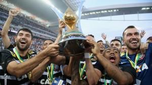 Malcom (derecha) sujetando el trofeo que acredita al Corinthians como el campeón de la Liga Brasileña en la temporada 2015. Imagen procedente de: img.fifa.com