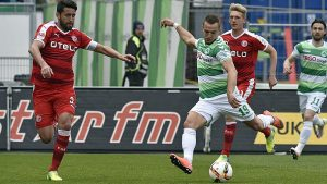 Berisha golpea el balón bajo la atenta mirada de Haggui. Foto: bundesliga.com